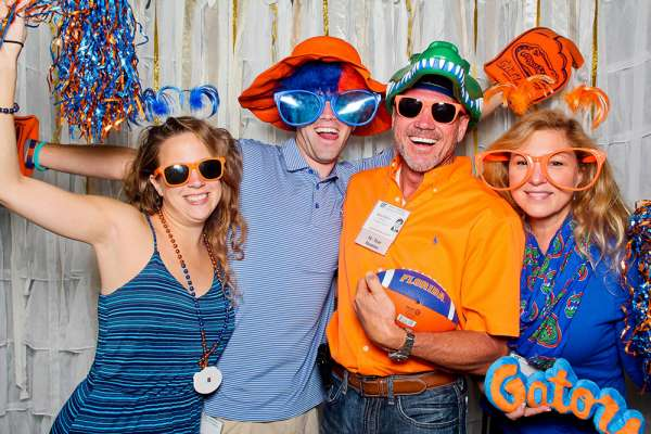 Alumni with Gator props posing for photo in photo booth